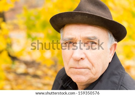Close up portrait of an elderly man looking at the camera with a serious expression wearing a stylish hat while enjoying time outdoors in a colourful autumn garden - stock photo