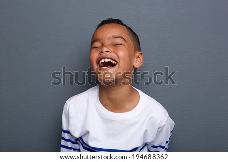 Close up portrait of an excited little boy laughing on gray background - stock photo