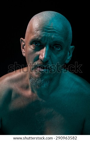 Close-up portrait of an old man. He is a strange and terrible.  Wicked eye and look of a madman. - stock photo