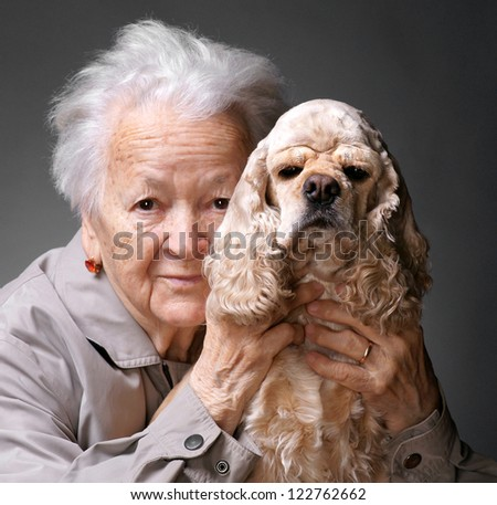 Close-up portrait of an old woman with american spaniel on a gray background