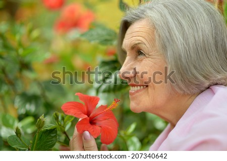 Close-up portrait of an older woman on walk with red flowers - stock photo