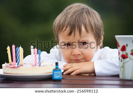 Close-up portrait of angry little boy with a cake and tea, outdoor