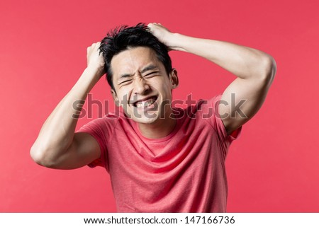 Close up Portrait of Asian man standing looking Anxious. Red background. - stock photo