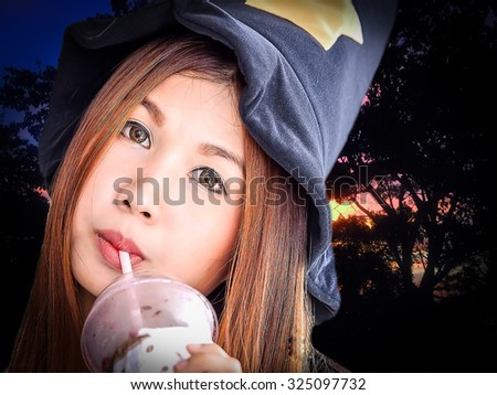close up portrait of Asian woman were black hat and drink ice coffee with sunset and silhouette of tree background - stock photo