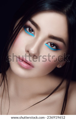 Close-up portrait of asian young girl with blue wings under hazel eyes and open lips looking at you on black background - stock photo