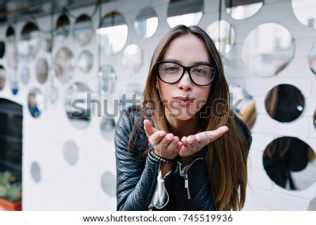 Close-up portrait of attractive brunette girl with long hair standing near white wall. She wears black jacket, stylish glasses. She is making a kiss to the camera.
