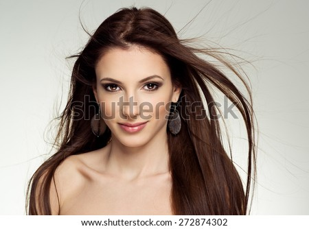 Close-up portrait of attractive Caucasian female salon model with flying hair. Young pretty fashion girl wearing stony earrings posing in studio.  - stock photo