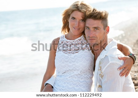 Close up portrait of attractive couple sitting on the beach.
