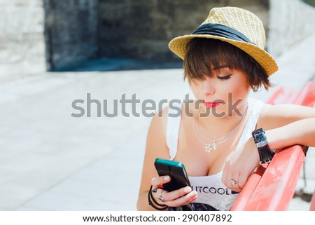 Close up portrait of attractive girl with shortcut dark-blonde hair. Wearing stylish summer hat, white top. Sitting on red bench with smartphone. Looking at mobile phone. Copy space. - stock photo