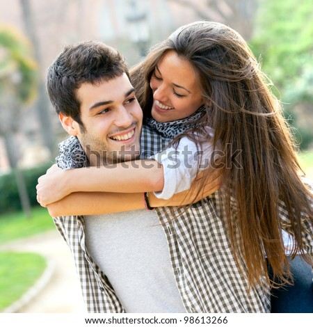 Close up portrait of attractive young couple piggybacking outdoors. - stock photo