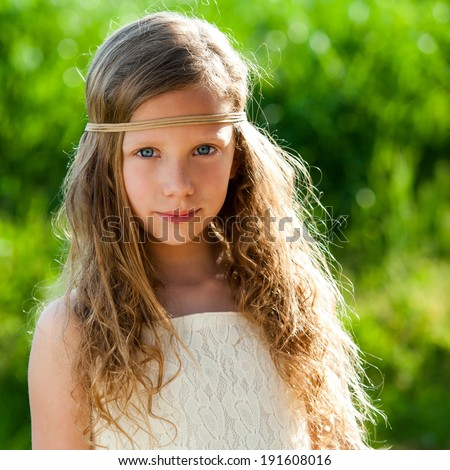 Close up portrait of attractive young girl wearing ribbon headband outdoors. - stock photo