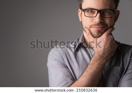 Close-up portrait of attractive young man holding chin. Man standing on gray background with glasses - stock photo