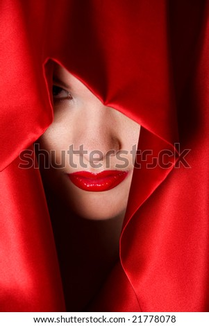 Close up portrait of attractive young woman in red hood - stock photo