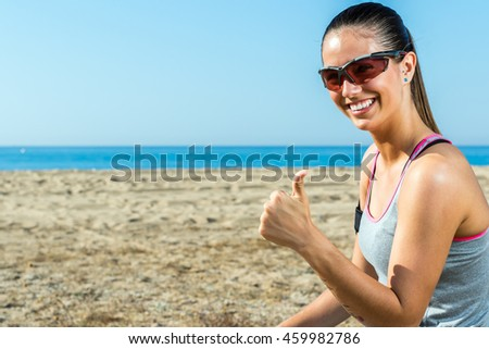 Close up portrait of attractive young woman in sportswear doing thumbs up outdoors.