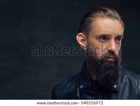 Close up portrait of bearded male looking up on a dark background.