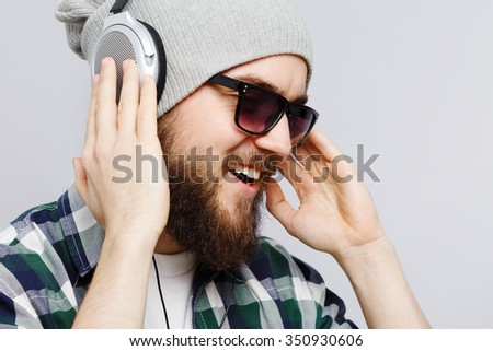Close up portrait of bearded man, wearing on white t-shirt, gray hat, sunglasses and blue checked shirt, listening to music on headphones and smiling, on white background, in studio - stock photo