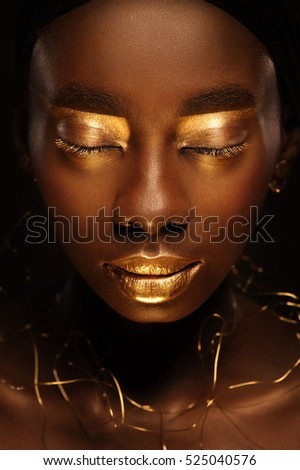 Close up portrait of beautiful african woman with creative gold make up and turban