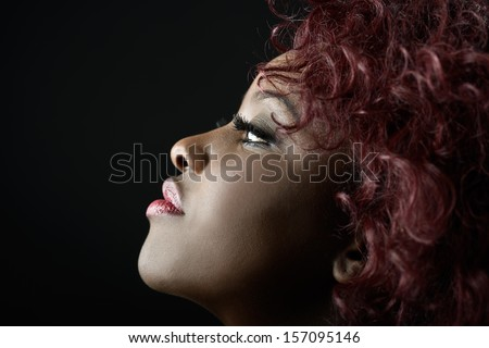 Close up portrait of beautiful black woman on black background with red hair. Afro hairstyle. Studio shot