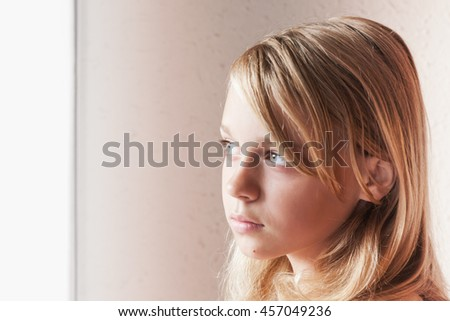 Close up portrait of beautiful blond Caucasian girl near a window with white curtains - stock photo