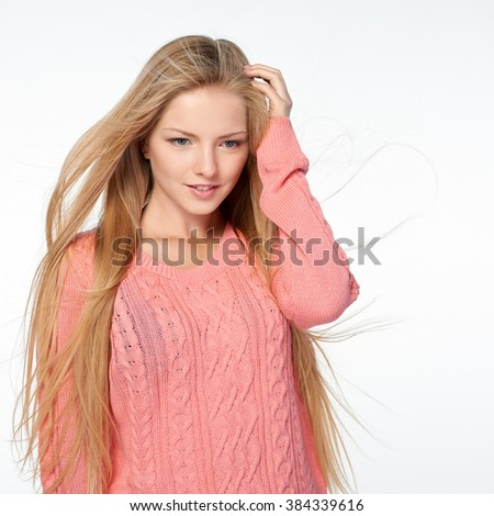 Close up portrait of beautiful blond female in pink sweater with hair lightly fluttering in the wind, over white background - stock photo