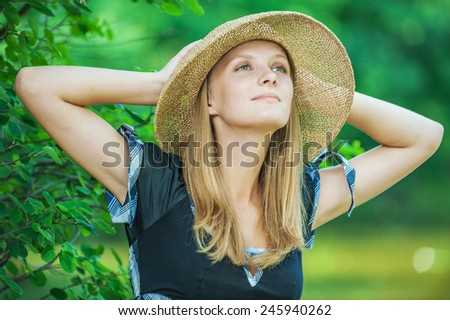 close-up portrait of beautiful blond woman wearing hat standing in park - stock photo