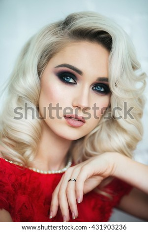 Close-up portrait of beautiful blonde girl in red dress - stock photo