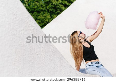 Close up portrait of beautiful blonde girl sitting outside with pink cotton candy. Wearing sunglasses with stars. Red lips. White background, not isolated. - stock photo