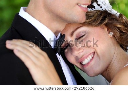 close up portrait of beautiful bride smiling while eyes closed - stock photo