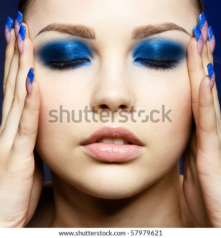 Close-up portrait of beautiful brunette with blue eye shadow make up and manicure - stock photo