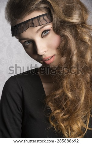 close-up portrait of beautiful brunette woman with black dress, nice make-up and long wavy healthy hair. Charming expression looking in camera  - stock photo