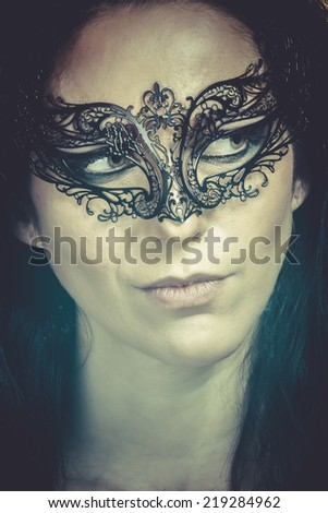 close-up portrait of beautiful brunette woman with carnival venetian mask
