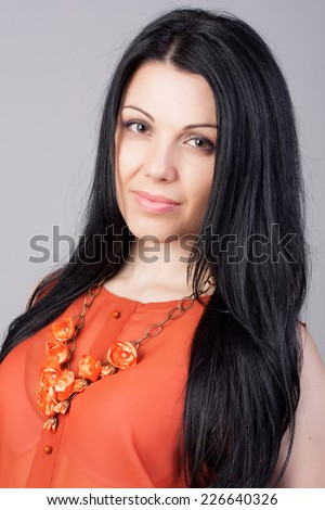 Close-up portrait of beautiful brunette woman with earring jewelry. Fashion photo. Long and healthy hair concept.