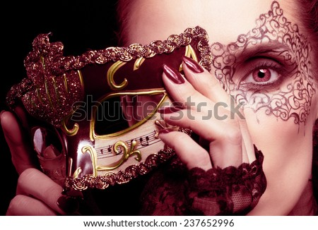 Close-up portrait of beautiful brunette woman with facial body art hiding half of her face with carnival venetian mask in marsala colors