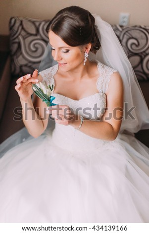 Close up portrait of beautiful caucasian mid adult bride holding cute little boutonniere - stock photo