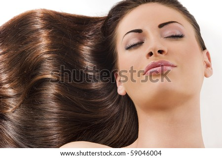 close-up portrait of beautiful female face keeping her eyes closed with long dark hairs laying down - stock photo