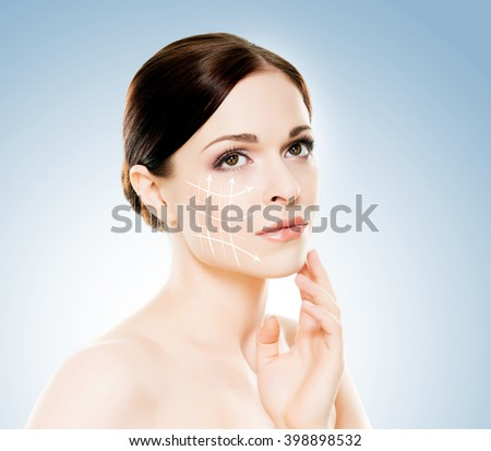 Close-up portrait of beautiful, fresh, healthy and sensual girl with arrows on her face. Medicine, spa and skin care concept. - stock photo