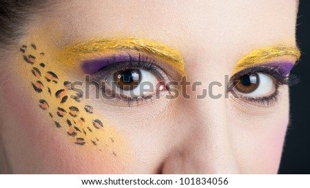 Close up portrait of beautiful girl eyes with leopard make up.