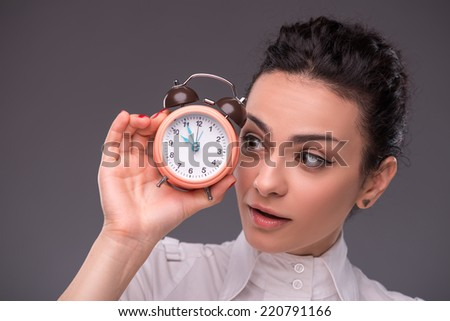 Close-up portrait of beautiful girl looking with interest on an alarm clock that is in her hand, with copy place isolated on grey background concept of time management