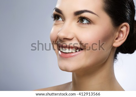 Close up portrait of beautiful girl with black fixed hair behind, big eyes and naked shoulders, looking left and smiling, close up, gray studio background.