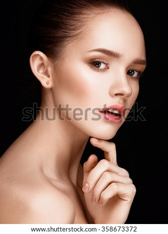 Close-up portrait of beautiful girl with clear healthy skin. Looking at the camera. Touching her face. Beauty studio shot. - stock photo