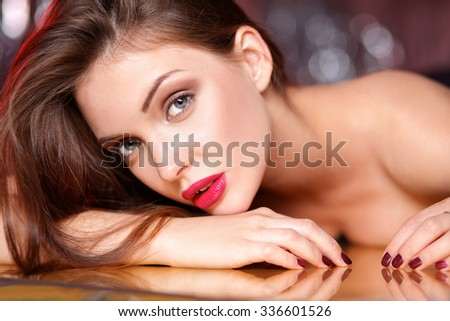 Close-up portrait of beautiful girl with trendy makeup lying - stock photo