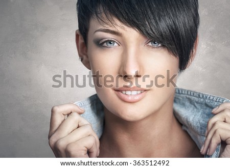 Close-up portrait of beautiful happy young woman on grey background - stock photo
