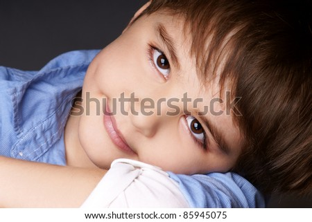 Close-up portrait of beautiful little boy with attentive look, studio shot