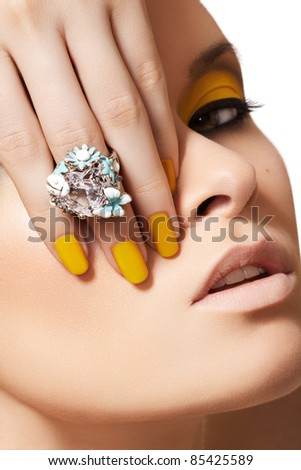 Close-up portrait of beautiful model face with neon yellow fashion make-up and with big crystal ring. Disco makeup and manicure, bright nail polish