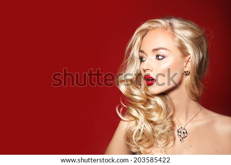Close-up portrait of beautiful model with long blonde hair on red background and big lips - stock photo