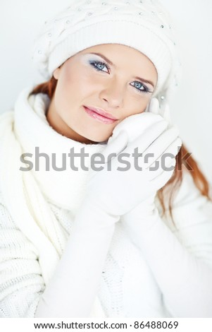 Close-up portrait of beautiful pure young woman wearing white winter clothing - stock photo