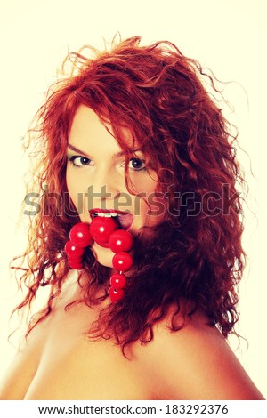 Close up portrait of beautiful redhead woman with big ,red,vintage, wooden beads - stock photo