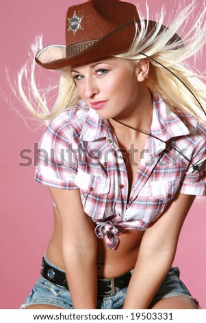 Close-up portrait of beautiful rodeo girl in cowboy hat on pink background