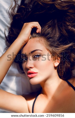 Close up portrait of beautiful sexy  brunette  smiling  woman  with perfect tan skin lying in bed in her underwear. Relaxing and enjoying  in her bedroom in the morning. - stock photo