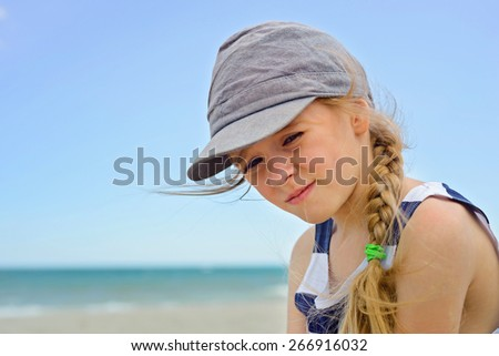 Close-up portrait of beautiful small girl in denim hat - stock photo
